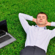 Stock Photo: Handsome mlaying on grass near laptop