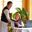Waiter giving menu to female costumer at the restaurant — Stock Photo