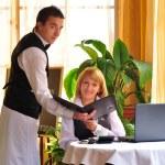 Waiter giving menu to female costumer at the restaurant — Stock Photo #12575185