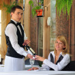 The waiter at the restaurant offers wine visitor — Stockfoto