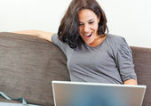 Cheerful woman in front of her laptop — Stock Photo