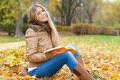 Smiling woman reading in a park in autumn — Stockfoto