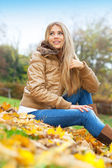 Blond woman sitting in a park — Stock Photo