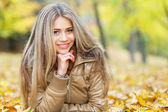 Smiling young woman in autumn — Stock Photo