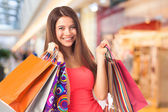Happy brunette with shopping bags — Stock Photo