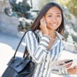 Young asian tourist on the phone and holding a city tour map — Stock Photo
