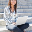 Portrait of an asian girl using a laptop outdoor — Stock Photo