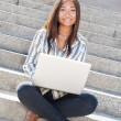 Happy asian girl using a laptop outdoor — Stock Photo