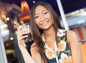 Smiling asian girl enjoying a soda on terrace — Stock Photo