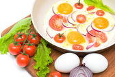 Fried eggs in a frying pan and vegetables on the cutting board — Stock Photo