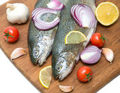 Trout, vegetables and lemon on a cutting board — Stock Photo