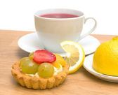 Cake, lemon and a cup of fruit tea on a white background — Foto de Stock