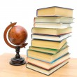 Antique globe and a stack of different books - Stock Photo