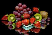 Winogrona, kiwi i truskawek na czarnym tle — Zdjęcie stockowe