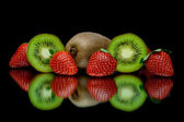 Strawberries and kiwi on a black background with reflection — Stock Photo