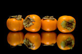 Persimmon on black background with reflection — Stock Photo