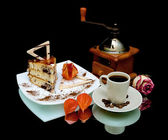 Cake and a cup of coffee on a black background with reflection — Stock Photo