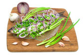 Herring, onions and garlic on a cutting board on a white backgro — Stock Photo