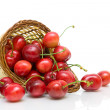 Ripe cherry in a wicker basket on a white background close-up. — Stock Photo