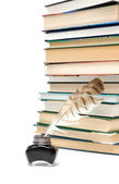 Quill in the inkwell and a large stack of different books on a w — Stock Photo