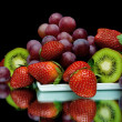 Still life of fresh fruit on a black background — Stock Photo