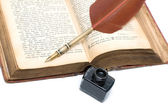 Inkwell, pen and open book on white background — Стоковое фото