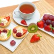 Tartlets with whipped cream and fruit, fresh fruit and a cup of  — Стоковая фотография
