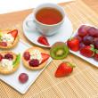 Tartlets with whipped cream and fruit, fresh fruit and a cup of — Stock Photo