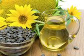Sunflower oil and sunflower flowers close-up — Stock Photo