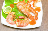 A piece of broiled fish, shrimp and red caviar on white plate cl — Stock Photo