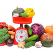 Stock Photo: Kitchen scale and vegetables isolated on a white background