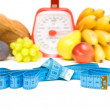 Measuring tape, kitchen scale and vegetables on a white backgrou — Stock Photo