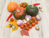 Ripe vegetables and autumn maple leaves on a wooden board — Stock Photo