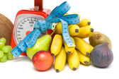 Fruit, kitchen scales and measuring tape close up. white backgro — Stock Photo