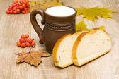 Pane e latte in una tazza su tavole di legno — Foto Stock