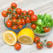 Ripe cherry tomatoes, lemon and salad frieze — Stock Photo