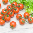 Ripe cherry tomatoes and salad frieze on a wooden table — Stock Photo #33980607