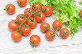 Tomates cereja maduros e friso de salada em uma mesa de madeira — Fotografia Stock