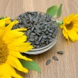 Sunflowers and ripe seeds close-up on a wooden board — Stock Photo
