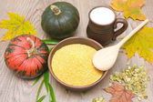 Corn grits, pumpkin and milk in a clay mug on a wooden table — Stok fotoğraf