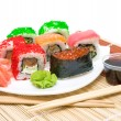 Stock Photo: Sushi with red caviar and rolls close up on white plate