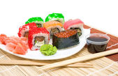 Sushi met rode kaviaar en rollen close-up op een witte plaat — Stockfoto