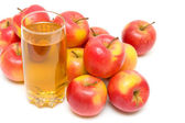 Ripe red apples and glass with juice close up on a white backgro — Stock Photo