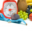 Measuring tape, scales and fruits on white background — Stock Photo