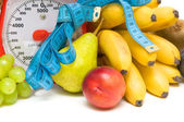 Measuring tape, kitchen scales and fresh fruit closeup. — Stock Photo