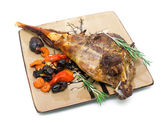 Baked leg of lamb with carrots, prunes and rosemary on a plate o — Stock Photo