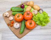 Vegetables on a cutting board on a wooden table closeup — Stock Photo