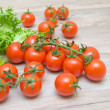 Cherry tomatoes and lettuce frieze close-up on a wooden table — Stock Photo #36842419