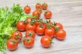 Cherry tomatoes and lettuce frieze close-up on a wooden table — Stock Photo