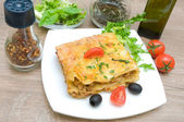 Lasagna with meat, cherry tomatoes, olives and spices on a woode — 图库照片